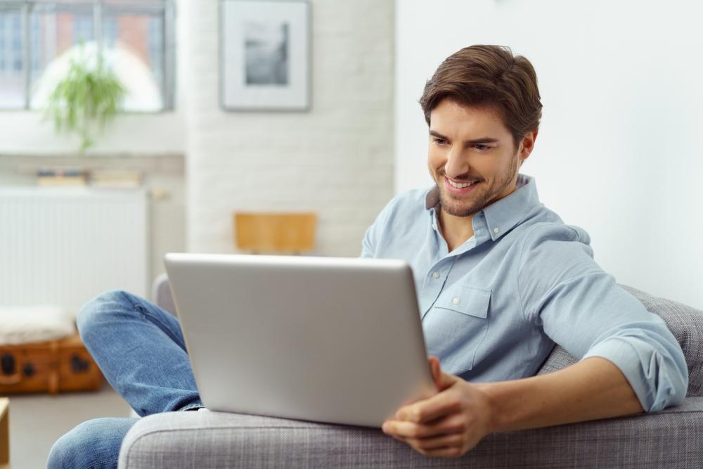 Junger Mann freut sich über das Spielen am Computer
