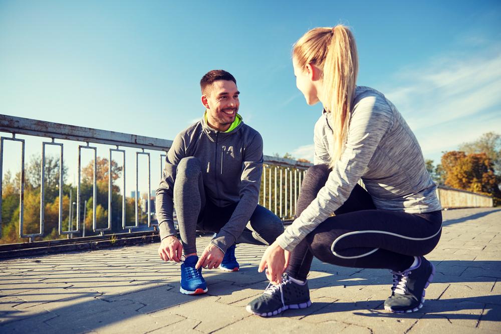 Glückliches Paar zieht sich Sportschuhe an