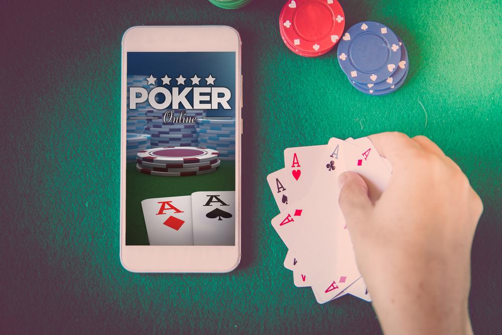 Mann legt Poker-Karten neben sein Handy