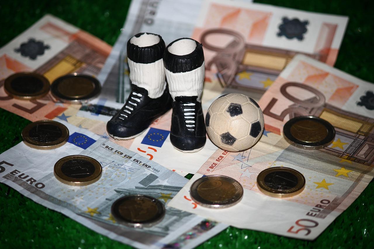Kleiner Fußball und Schuhe stehen auf Geldscheinen.